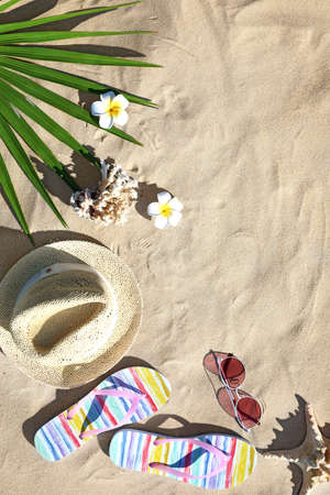Flat lay composition with different beach accessories on sand. Space for text Zdjęcie Seryjne