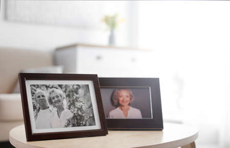 Portraits in stylish frames on table indoors Stock fotó