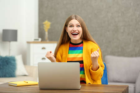 Happy young woman playing online lottery using laptop at home Stock Photo