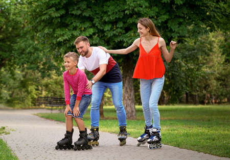 Young happy family roller skating in summer park