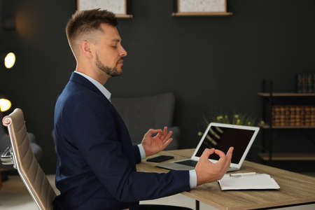 Businessman practicing zen yoga at table in office Фото со стока