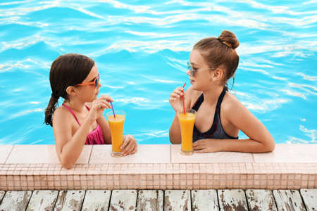 Happy girls with drinks in swimming pool