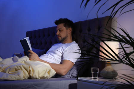 Handsome man reading book in dark room at night. Bedtime