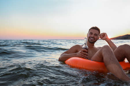 Happy young man with drink on inflatable ring in water 版權商用圖片 - 130144499