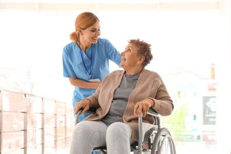 Nurse assisting elderly woman in wheelchair indoors 스톡 콘텐츠