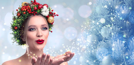 Beautiful young woman with Christmas wreath blowing magical snowy dust on blurred background. Bokeh effect Standard-Bild - 130144513