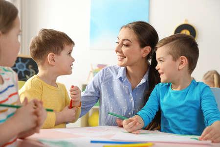 Bambini piccoli con maestra d'asilo che disegna al tavolo al chiuso. Imparare e giocare