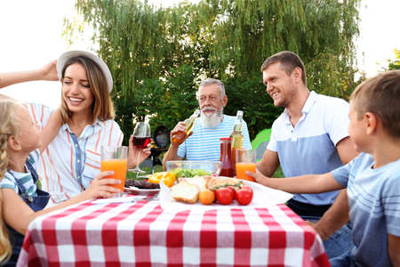 Happy family having barbecue in park on sunny day Stockfoto
