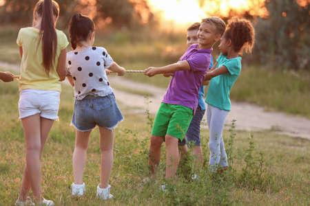 Süße kleine Kinder, die bei Sonnenuntergang im Freien spielen Standard-Bild