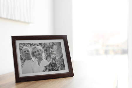 Portrait of senior couple in frame on table indoors. Space for text Stockfoto