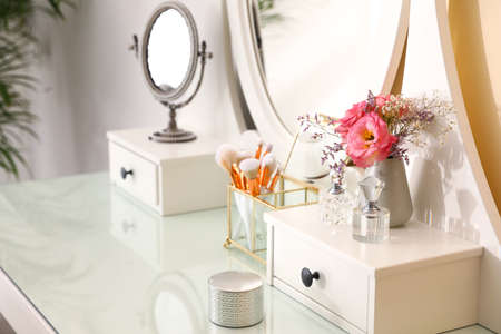 Modern dressing table with flowers in stylish room interior Stock Photo
