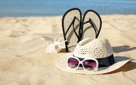 Stylish beach accessories on sand near sea