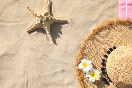 Straw hat and starfish on sand, top view with space for text. Beach accessories