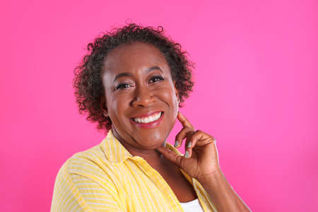Portrait of happy African-American woman on pink background