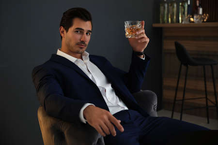 Young man with glass of whiskey in bar