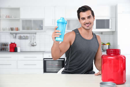Young athletic man with protein shake powder in kitchen, space for text