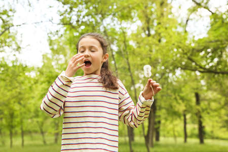 Little girl with dandelions suffering from seasonal allergy outdoors on sunny day