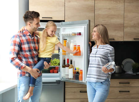 Happy family with bottle of water near refrigerator in kitchen Stockfoto