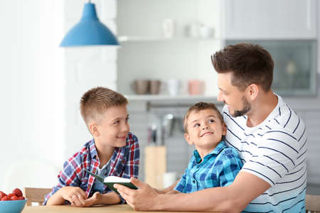 Dad and his sons reading interesting book in kitchen