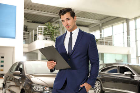 Young salesman with clipboard near car in modern dealership