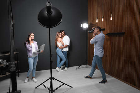 Professional photographer with assistant taking picture of young couple in modern studio Фото со стока