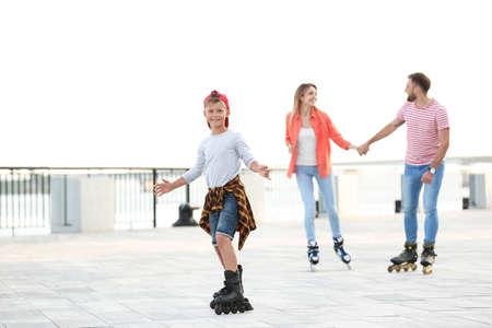 Happy family roller skating on city street Reklamní fotografie - 132239699