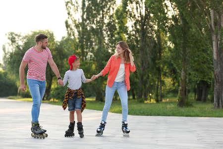 Happy family roller skating on city street. Space for text Reklamní fotografie