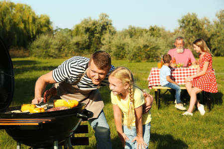 Father with little girl at barbecue grill and their family in park