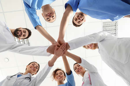 Team of medical workers holding hands together in hospital, bottom view. Unity concept Zdjęcie Seryjne