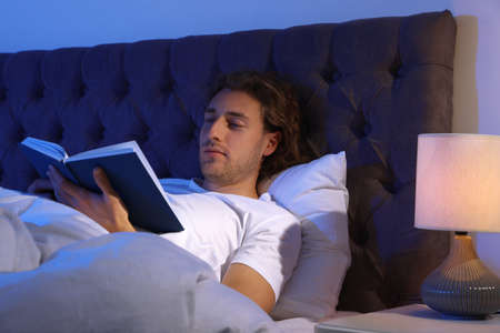 Handsome young man reading book in dark room at night. Bedtime Banque d'images - 131767954