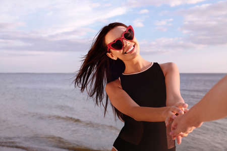 Young woman holding hands with girlfriend on beach