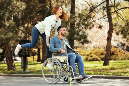 Young man in wheelchair and joyful woman at park
