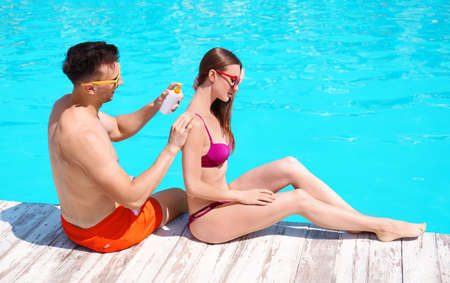 Young man applying sun protection cream onto girlfriend at swimming pool 스톡 콘텐츠