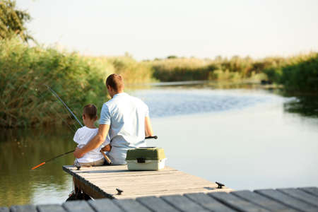 Dad and son fishing together on sunny day. Space for text