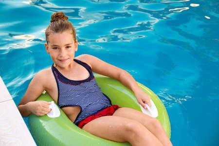 Niña feliz en anillo inflable en piscina Foto de archivo