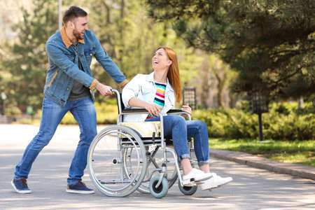 Happy woman in wheelchair and young man at park on sunny day