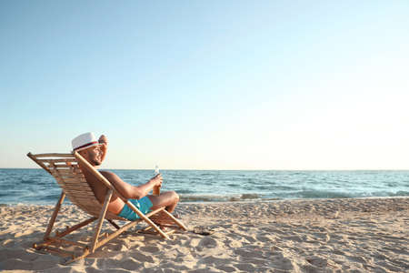 Young man relaxing in deck chair on beach near sea
