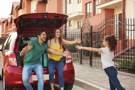 Cute girl running to her parents near family car on street Reklamní fotografie