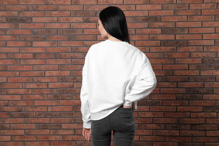 Young woman in sweater at brick wall. Mock up for design Foto de archivo - 129993984