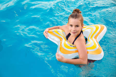 Happy little girl with inflatable ring in swimming pool