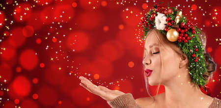 Beautiful young woman with Christmas wreath blowing magical snowy dust on red background. Bokeh effect