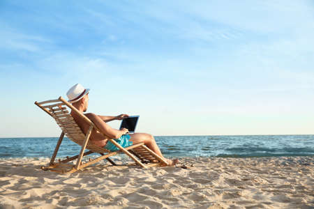 Young man with laptop in deck chair on beach 版權商用圖片