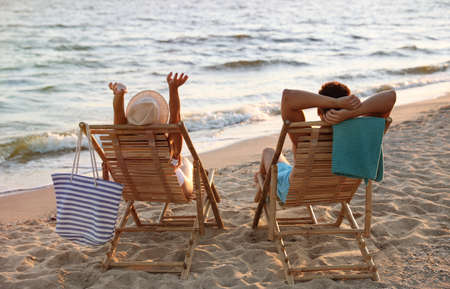 Young couple relaxing in deck chairs on beach near sea 版權商用圖片