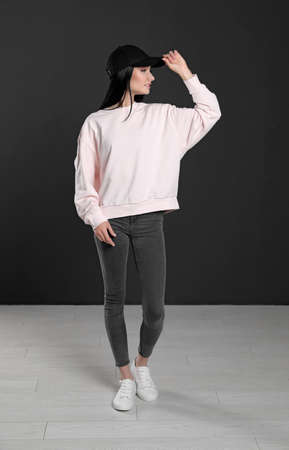 Full length portrait of young woman in sweater at black wall. Mock up for design Foto de archivo - 129994075