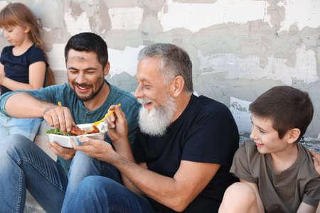 Pauvres gens tenant des assiettes avec de la nourriture près du mur à l'extérieur