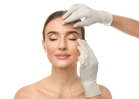 Doctor examining woman's face before plastic surgery on white background