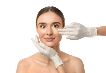 Doctor examining woman's face before plastic surgery on white background Stock Photo