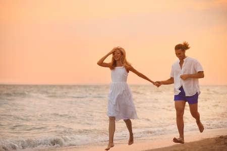 Młoda para bawi się na plaży o zachodzie słońca