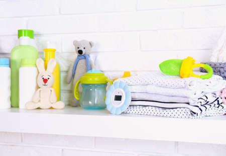 Baby accessories on shelf near white brick wall