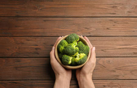 Female holding bowl of fresh green broccoli on wooden table, top view. Space for text Stock Photo